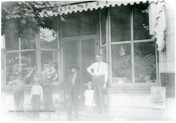 'Mr. Hogsett, proprieter, on right.'  Children and others in front of store.