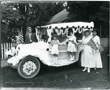 Man, two children, and two women stand near a car decorated for the Fourth of July parade.