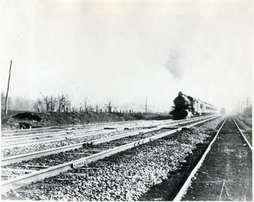 Train moving down tracks. 'Credit; Mrs. Cecile Huffman.'