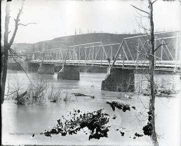 Two men standing on old iron bridge looking south.
