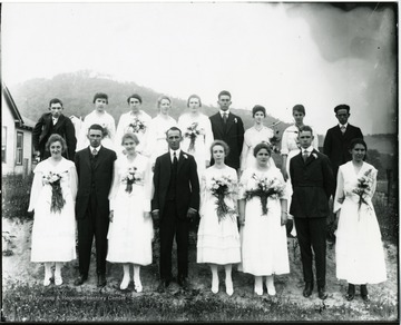 Group portrait of girls in white dresses with bouquets attached in front and boys in dark suits.
