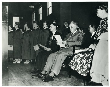 'President F.D. Roosevelt is listening to the graduating class of Arthurdale High School singing. On the left is E. Grant Nine, principal of the High School.' Eleanor Roosevelt