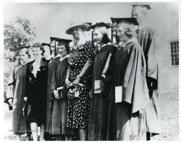 Mrs. Eleanor Roosevelt is standing with the graduating class and teacher at Arthurdale.