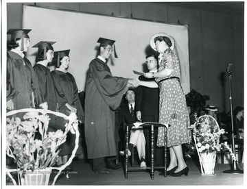 Mrs. Eleanor Roosevelt shakes the hand of a graduate and hands out diplomas during the graduation ceremony at Arthurdale High School in Arthurdale, West Virginia.  Jennings Randolph visible on the stage.