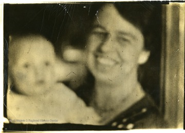 Blurry view of Eleanor Roosevelt and a baby. 'Eleanor Roosevelt makes talkies for farewell speech.'