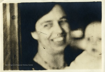 Blurry image of Eleanor Roosevelt and a baby. 'Mrs. Eleanor Roosevelt makes talkies for farewell speech.'