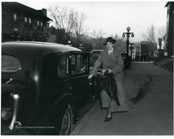 Mrs. Eleanor Roosevelt is getting into a car parked in front of the Hotel Morgan. Richard Restaurant is across the street.