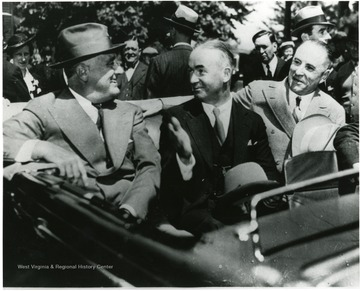 FDR speaks with Senator Matthew M. Neely and Governor Homer A. Holt while riding in a car at Reedsville, W.Va. during visit to the Arthurdale. 'A Print from the Franklin D. Roosevelt Library Collection.  This print is furnished for your file and must not be reproduced without the owner's permission.'
