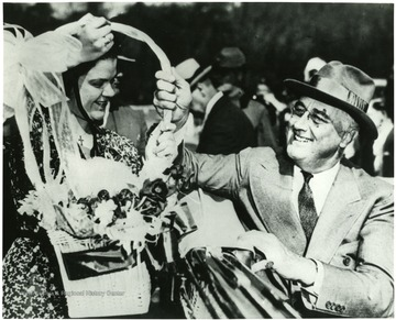 Franklin D. Roosevelt accepting flowerbasket from a high school graduate in Arthurdale W. Va. 'A print from the FDR Library Collection. this print is furnished for your file and must not be reproduced without the owner's permission. Owner: UPI (Acme).'