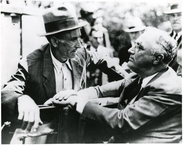 Franklin Roosevelt sits in car listening intently to homesteader M. L. Perkins in Arthurdale, W. Va. 'A print for the FDR Library Collection. This print is furnished for your file and must not be reproduced without the owner's permission. Owner: UPI (acme).'