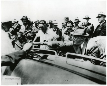 Large crowd gathers around the car of Franklin D. Roosevelt as he leans to pet A cow of local farmer. 'A print from the Franklin D. Roosevelt Library Collection.  This print is furnished for your file and must not be reproduced without the owner's permission.  Owner:  UPI (Acme)' On 6/8/05 spoke with Mark Renovitch, archivist, Roosevelt Library who stated that reproduction of this image is alllowed for personal or research use. If the image is to be published , permission must be attained from the Bettman Archive, owned by Corbis, which now posseses the U.P.I. photo archive.