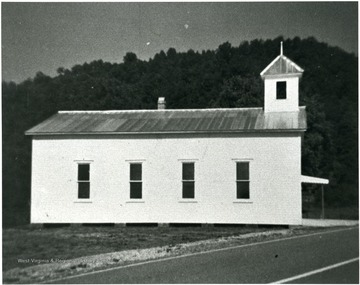 White church next to a road.  Four windows visible.