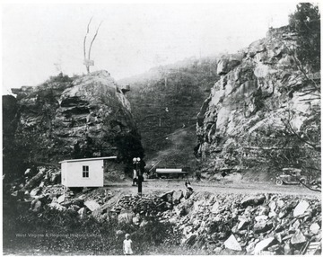 A lady sits on a boulder from the blasting to make Falls Mill Rd.