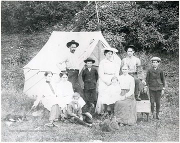 Lockard family poses for a picture next to their white camp tent.