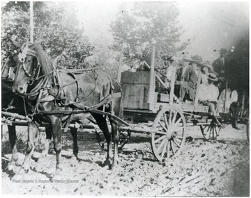 Lockard family members seated in wagon pulled by horses.