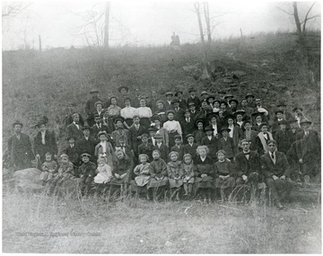 Students and parents lined up in a field for a group portrait.