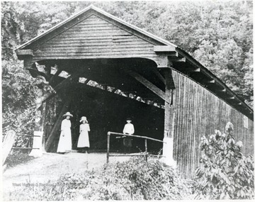 Three people stand in the entrance to the Bulltown bridge.