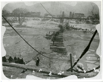 Cables and wooden bridge has fallen into the Elk River. People line the shore and bank of river to watch the rescuing of people from the bridge.