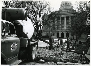Workers lay concrete outside the capitol building.