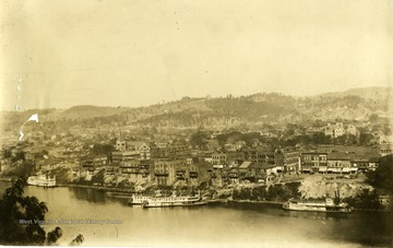 A picture postcard of Charleston, West Virginia.  Boats along shore of river.