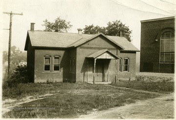 Small brick schoolhouse with gabled entrance.  Stansbury Hall is visible in the right side of the photograph.  In the 1940s and 50s, West Virginia University used this school as a grade school for training eductaion majors.  It was called the WVU Laboratory Elementary School. The building was an African-American school prior to WVU's use of the building.