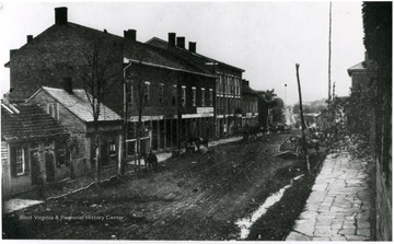 View of unpaved streets, stone sidewalks, and old buildings that lined Main Street in Clarksburg in 1863.