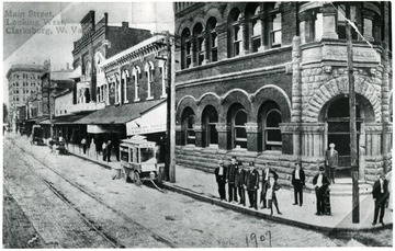 Townspeople are standing in front of buildings located on Main Street, looking west, in Clarksburg, West Virginia.