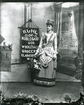 Advertisement for Ruhl Koblegard and Co. Wholesale Grocery, in Clarksburg, West Virginia, featuring a girl wearing an ornate dress and holding a basket of flowers.