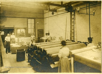 Women work with machinery inside the Empire Laundry Company.