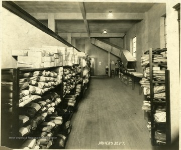Interior view of the Empire Laundry Company in Clarksburg.  Wrapped packages line the shelves of the drivers department.