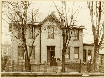 Sheriff Residence: 1896-1900 Facing Back Street now Washington Avenue. Three women standing in front of the house: Elizabeth Bond Lang (Wife John G. Lang) Etta Lang (Wife of F. Shuttleworth) Susan Hornor Lang (Wife of Sheriff Lq.L. Lang).
