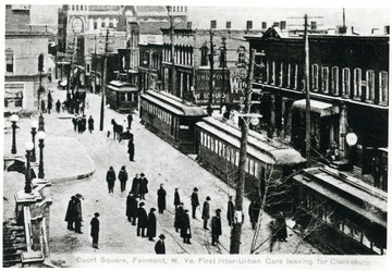 People on sidewalks next to trolley cars traveling in downtown Fairmont.