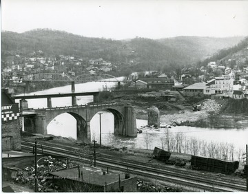 View of Grafton, West Virginia.  Railroad tracks in foreground. There are bridges - one being demolished, businesses, and houses along the river.