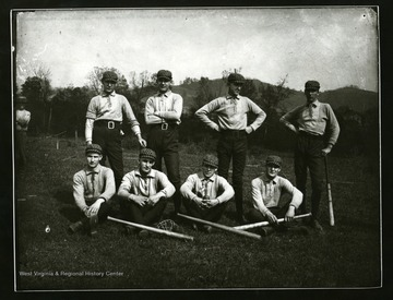 Baseball team members pose for a group portrait.