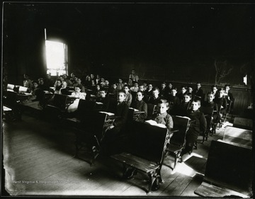 Students seated at their desks, teacher standing at the back of the classroom.