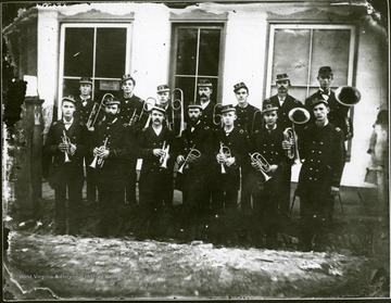 Group portrait men in uniform with brass musical instruments.