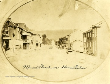 The back of a horse drawn wagon is seen moving down the dirt paved Main Street.