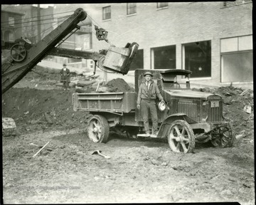 Man stands on runningboards of a truck that is being loaded with dirt.