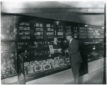 Interior view of C. G. Turner's Store in Grafton, W. Va.  Man looking at cigars on top of a counter while woman attendant waits.