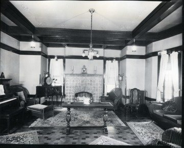 Interior view of the Bartlett living room with fireplace, piano and furniture.