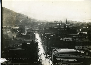 People are walking down an unidentified street in Wheeling, West Virginia, after a flood, possibly of 1913.