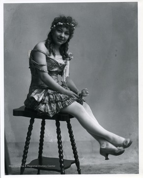 Woman wearing a dress and holding a flower is sitting on a stool.