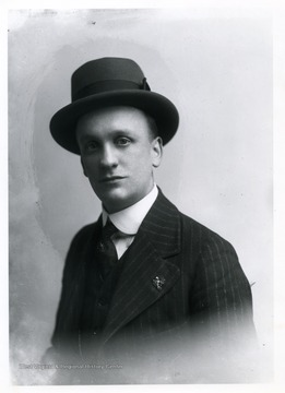 Man wearing a three-piece suit posing for a photograph.