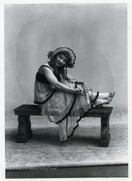 A woman wearing a dress and hat is sitting on a bench.