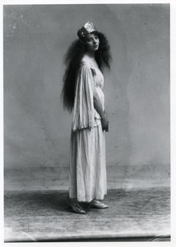 A woman with long curly hair is standing.