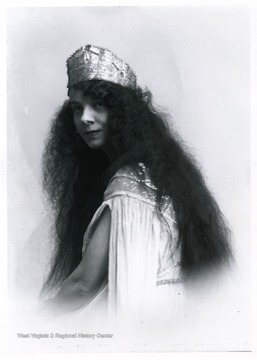 A woman with long curly hair is sitting.