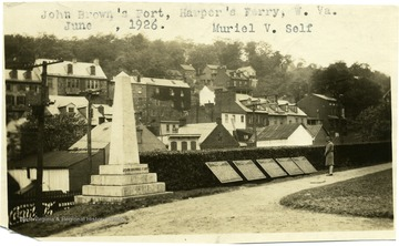 A woman reads the historic markers next to a monument to John Brown's Fort in Harpers Ferry, W. Va. 'Muriel V. Self.""