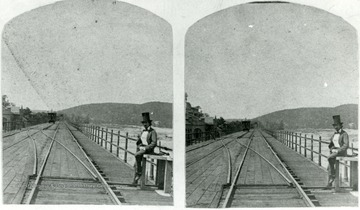 Unidentified man stands on a railroad track with the Potomac River behind him, 'Armory building on original site to left'.