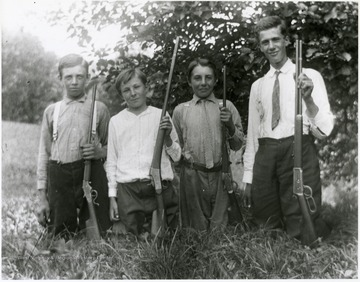 Group portrait of four boys kneeling in the grass, each holding a gun.