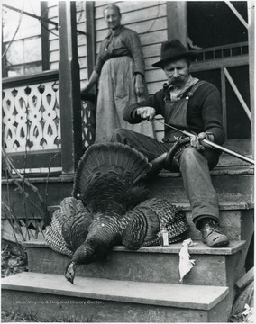 Gottfried cleaning out his gun by a dead turkey while Marianne Aegerter is watching.  Helvetia, W. Va.
